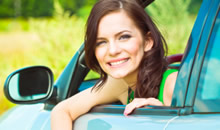 Photo of a woman smiling and looking out the open car window